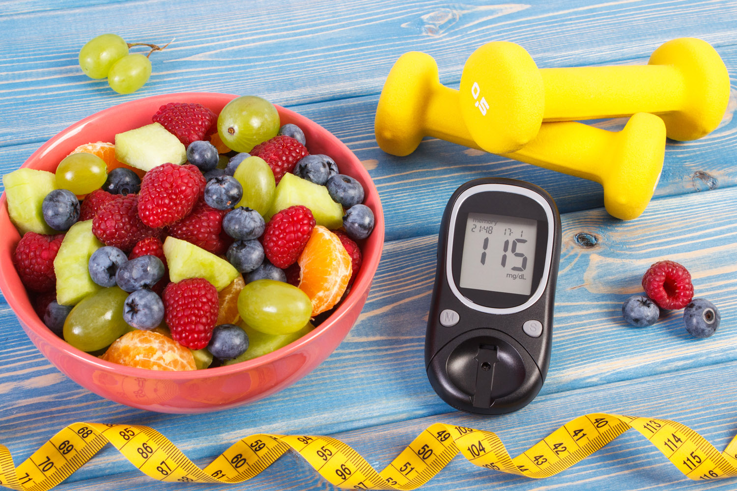 Fresh fruit salad, glucose meter with result of sugar level, tape measure and dumbbells for fitness, concept of diabetes, sport, slimming, healthy lifestyles and nutrition